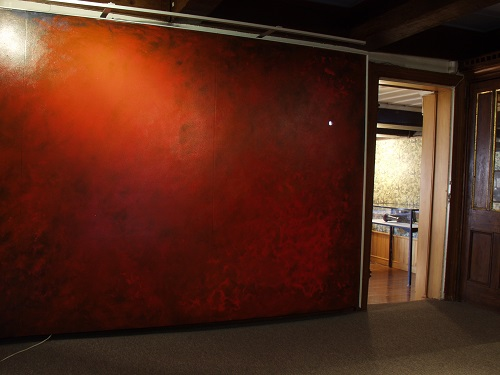 A. M. HOCH, interstices, site-specific installation at Alice Austen House Museum (2002): September 11 Mural, in entry to Alice Austen House; painted with acrylic glazes, with small eye hole cut out to see imbedded video of harbor shoreline, 2002