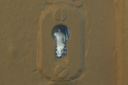 A. M. HOCH, interstices, DETAIL: Detail of keyhole (in door in living room leading to secret staircase) with embedded video of a woman walking upstairs; approximately 0.5 inches in diameter; 2002