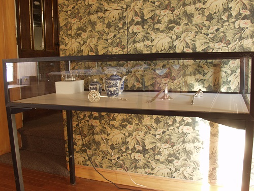 17. A. M. HOCH, interstices, DETAIL: dining room with glass case of objects including sugar bowl with embedded video, 2002